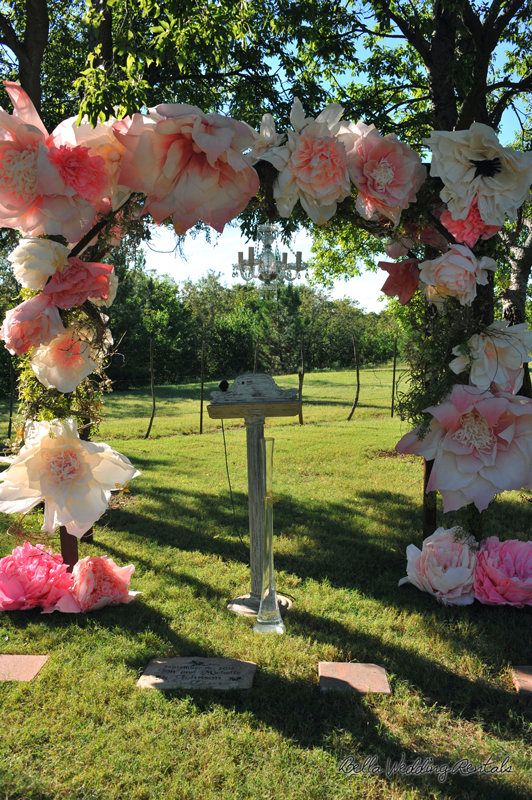 Wood arch with paper flowers and greenery