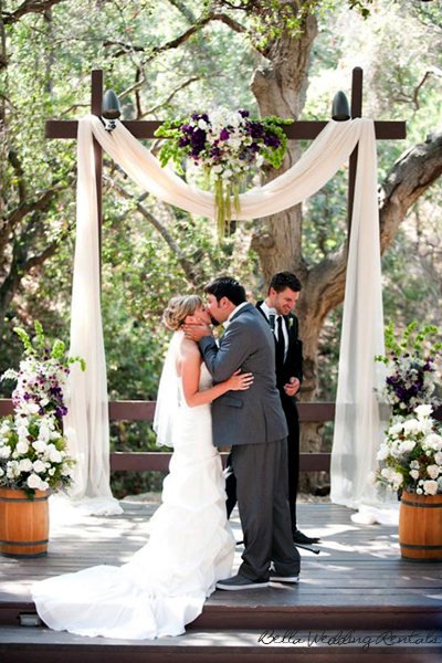 fabric and flower decorated wedding arch